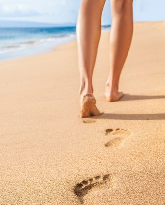 Beach travel – woman relaxing walking on sand beach leaving footprints in the sand. Closeup detail of female feet and legs on golden sand on Kaanapali beach, Maui, Hawaii, USA.